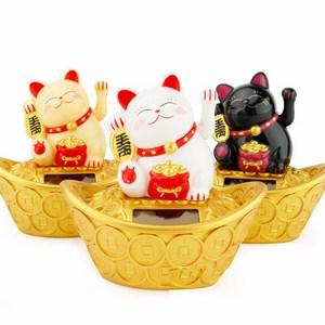 Chú mèo may mắn ngồi trên thỏi vàng